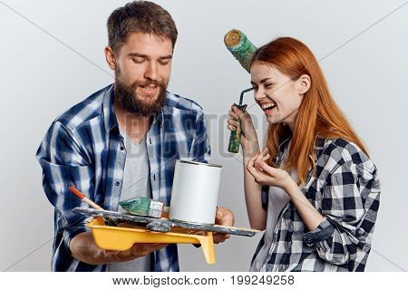 Beautiful young woman with a bearded man on a light background holding construction tools.