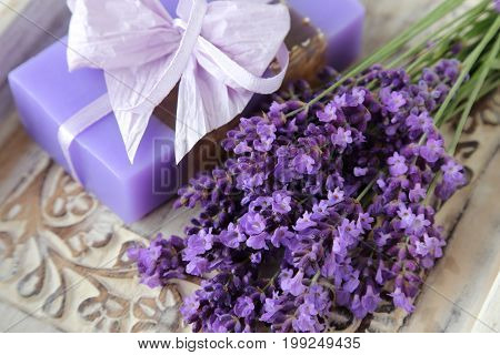 Bouquet of lavender and lavender soap on a wooden background.