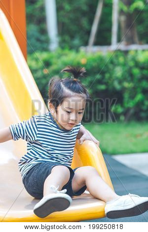 Cute Boy Is Playing Slider In Playground.