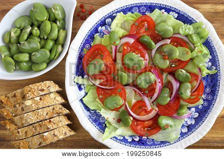 Salad with broad beans tomatoes and red onion.