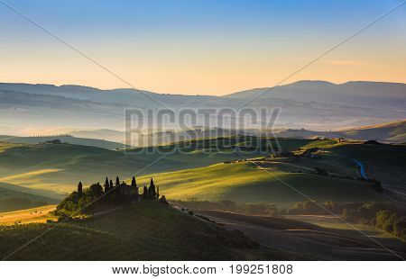 The rolling hills and green fields at sunrise Tuscany Italy