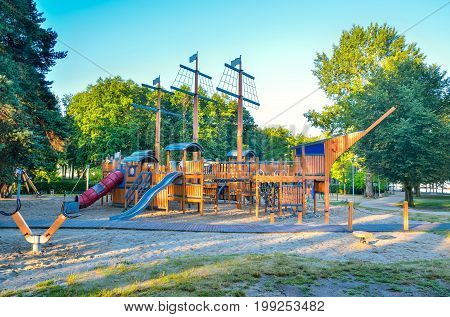 Beautiful playground for children on the lake. Wooden playground in the shape of a ship.