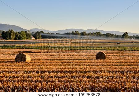 Summer rural landscape. Haystack in a meadow with mountain landscape.