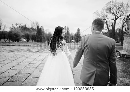 Beautiful Wedding Couple Walking On The Pavement On A Rainy And Cloudy Day. Black And White Photo.
