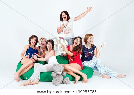 Girls in pajamas posing in studio. Happy female friends making pajama party. Women day, celebration, friends, bachelorette party, friendship, birthday and holidays concept