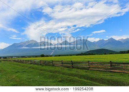 An old fence protects a beautiful green glade with yellow flowers amidst the mountains