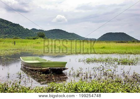 wood boat on pond and mountain landscape background on summer season in peaceful feeling