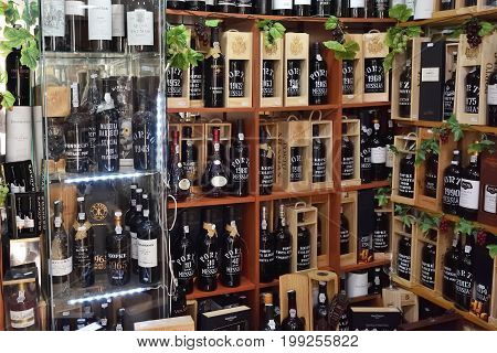 Cascais Portugal - June 13 2017: Shelves with varieties sorts of elite bottles of port wine in the wine store. Port wine is a Portuguese fortified wine produced exclusively in the Douro Valley in the northern provinces of Portugal