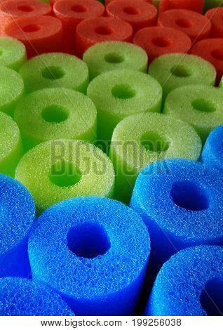 Foam noodles for swimming pools, lakes and the ocean are arranged by color at a retail store during the summer season