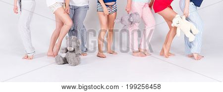 Girls in pajamas posing in studio. Female friends making pajama party. Women day, celebration, friends, bachelorette party, friendship, birthday and holidays concept. Unrecognizable women, only legs