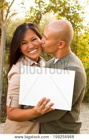 Loving Asain couple holding a sign outside.