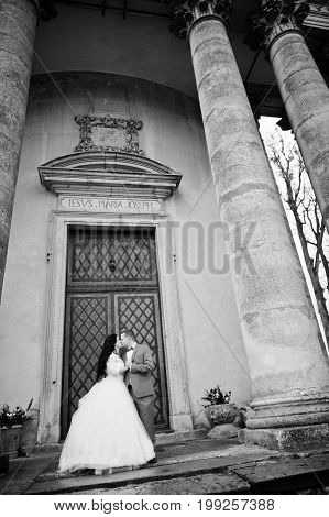 Stunning Wedding Couple Posing Next To The Ancient Doors Of A Castle. Black And White Photo.