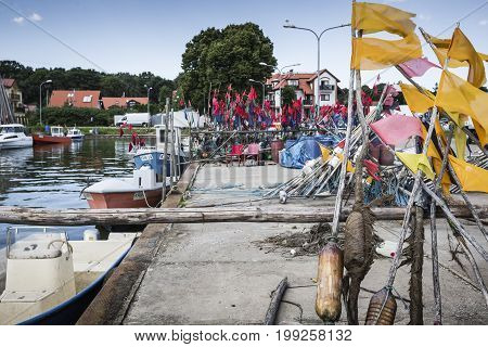 Network Fishing Drying On The Beach In Sunny Day. Baltic Sea And Fishing Boats In Background. Krynic