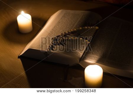 A candle a bible and a cross a rosary on a wooden table