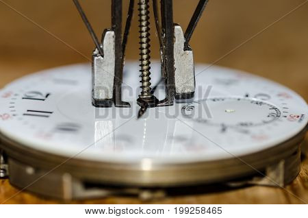Watch Repair: Hands Remover About to Lift The Hands from a Pocket Watch Movement