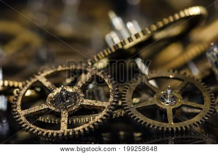 Watch Parts: Dirty and Grimy Vintage Metallic Watch Gears on a Black Surface