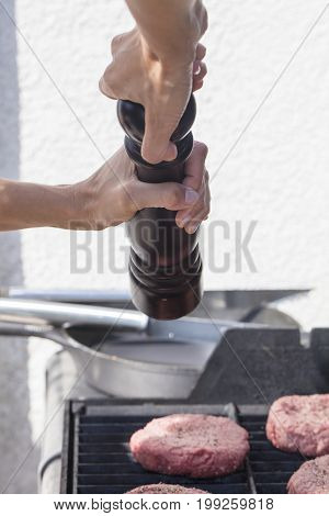 Barbecued hamburgers being seasoned on the grill