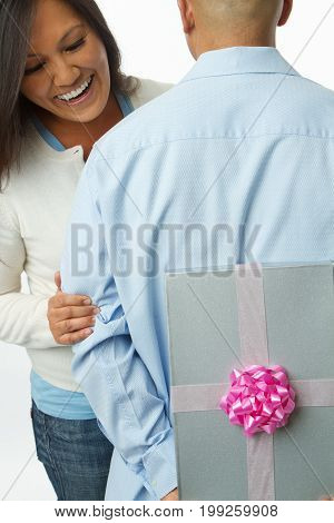 Happy Asian man surprising his wife with a gift.
