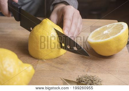 Person making salted preserved lemons by cutting and spicing