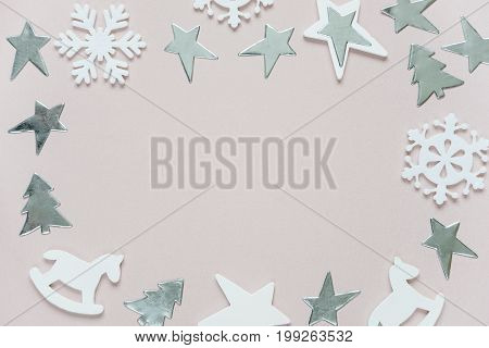 Christmas frame composed of white christmas decoration: snowflakes stars Christmas trees and toy; rocking horse on pink background. Flat lay composition for greeting card websites social media magazines bloggers artists etc.