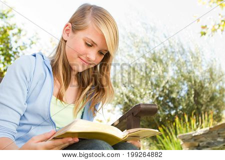 Young teen girl outside reading in the backyard.