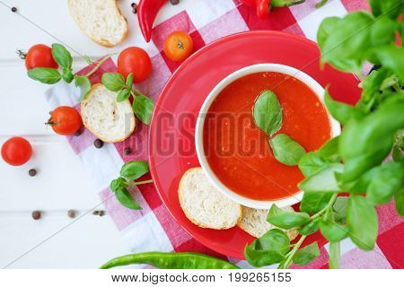 Cold summer tomato dish. Gaspacho soup with toast cherry tomatoes pepper basil herbs.