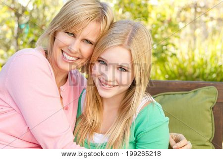 Portrait of a happy mother and her teenage daughter smiling.