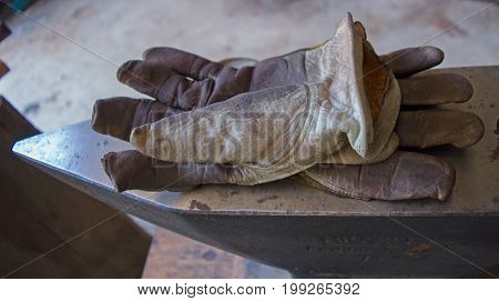 Moving on to other chores the blacksmith leaves his well used gloves on top of the metal anvil inside the workshop.