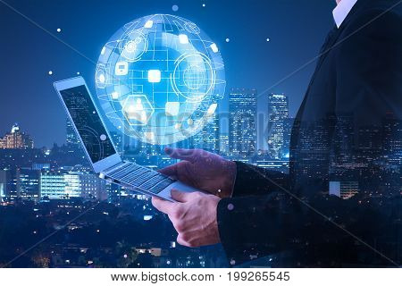 Attractive young adult businessman using laptop computer with abstract business hologram on nigth city background. Interface and communication concept. Double exposure