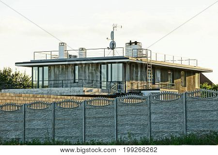 Gray private house behind a concrete fence