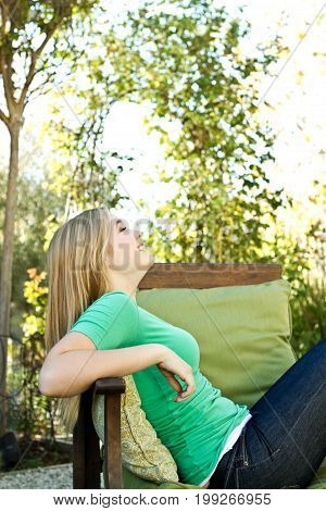 Happy young teen girl outside in the backyard.