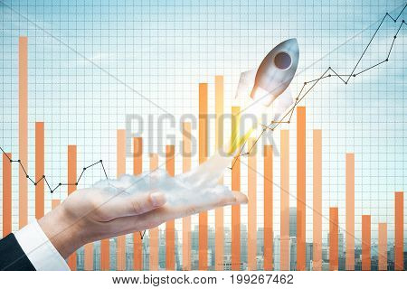 Businessman hand holding abstract launching rocket on city background with business chart. Start up and entrepreneurship concept. Double exposure