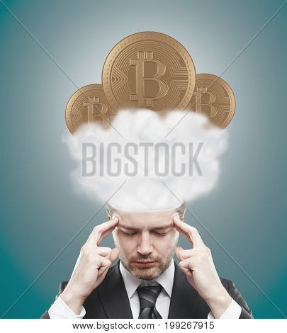Handsome young european man thinking about bitcoins in clouds on blue background. E-commerce concept