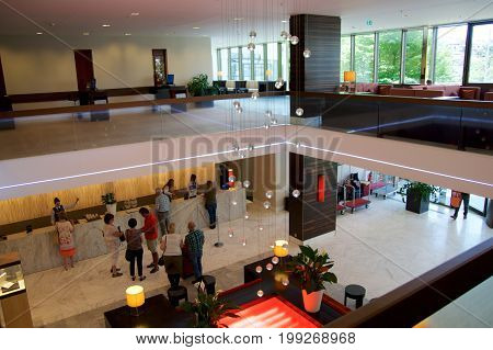 MAINZ, GERMANY - JUL 8th, 2017: Modern interiors of the lobby at Hilton Mainz Hotel with people waiting in line.