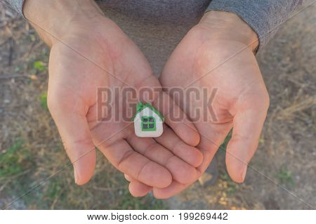 Man's hands hold small plasticine toy house on the background of ground. Buying a house concept.