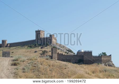 Old brown stone fortress with battlements on the background of the blue sky. Sudak Crimea