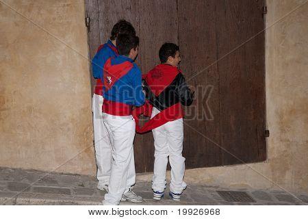 Three youths prepare in the street for Festa Dei Ceri