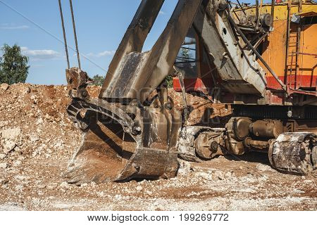 Bucket of an excavator on an industrial quarry, close-up