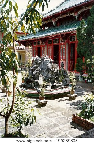 The courtyard of the Kwan Im Thong Hood Cho Temple, in Singapore, features a fountain display and several potted plants.