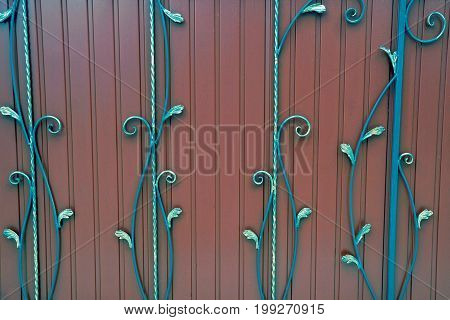 A fragment of red iron doors with wrought iron rods and a beautiful pattern