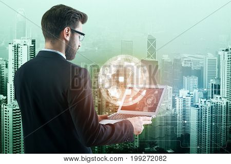 Attractive young adult businessman using laptop computer with abstract business hologram on nigth city background. Interface and technology concept. Double exposure