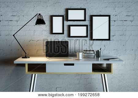 Close up of creative designer desktop with blank notebook coffee cup lamp picture frames and other items on white brick wall background. Mock up 3D Rendering