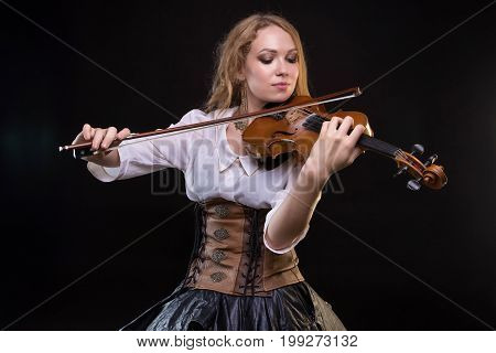 Blond young girl playing the fiddle on black background