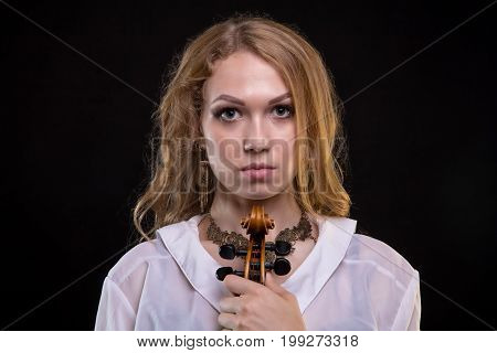 Young blond girl with fiddle on black background