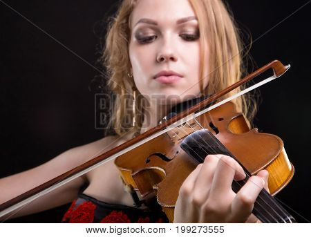 Closeup photo of woman playing the fiddle on black background