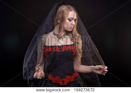 Blond girl with black veil on black background