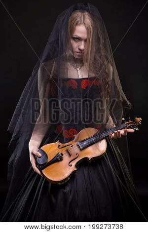 Blond young girl with black veil holding violin on black background