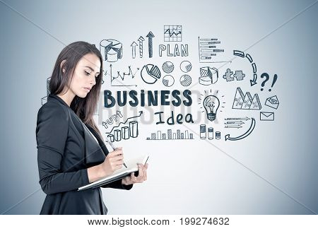 Portrait of a beautiful young businesswoman wearing a black suit and holding a planner and a pen taking notes. Gray wall background with a black business idea sketch on it.