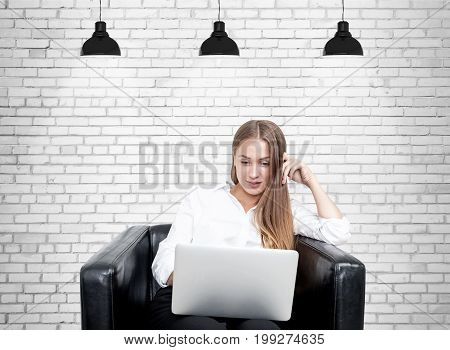 Portrait of a blonde businesswoman wearing a white blouse and sitting in a leather armchair with her laptop. She is looking at the screen with an amused expression. Brick wall background