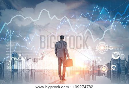 Rear view of an African American businessman holding a suitcase and looking at a morning cityscape with graphs and HUD. Toned image double exposure mock up